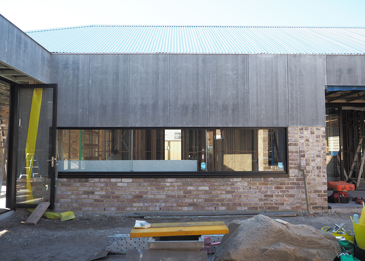 Photo Of A Wall Under Construction With Fiber Cement Above The Window And Brick Below.