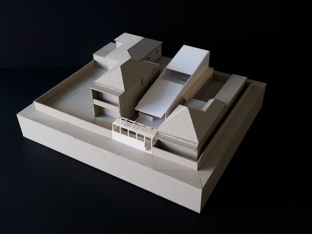 Image of a cardboard model of a house in street context.