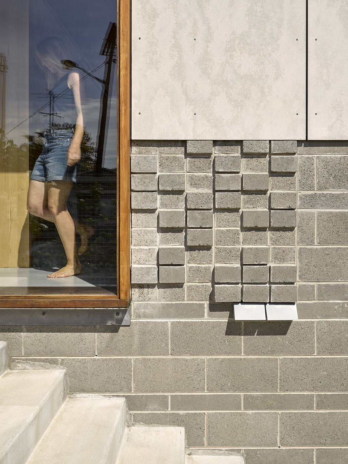 Image Of Blockwork Detail Above A Wall Light And A Person Depending A Stair Seen Through The Window.