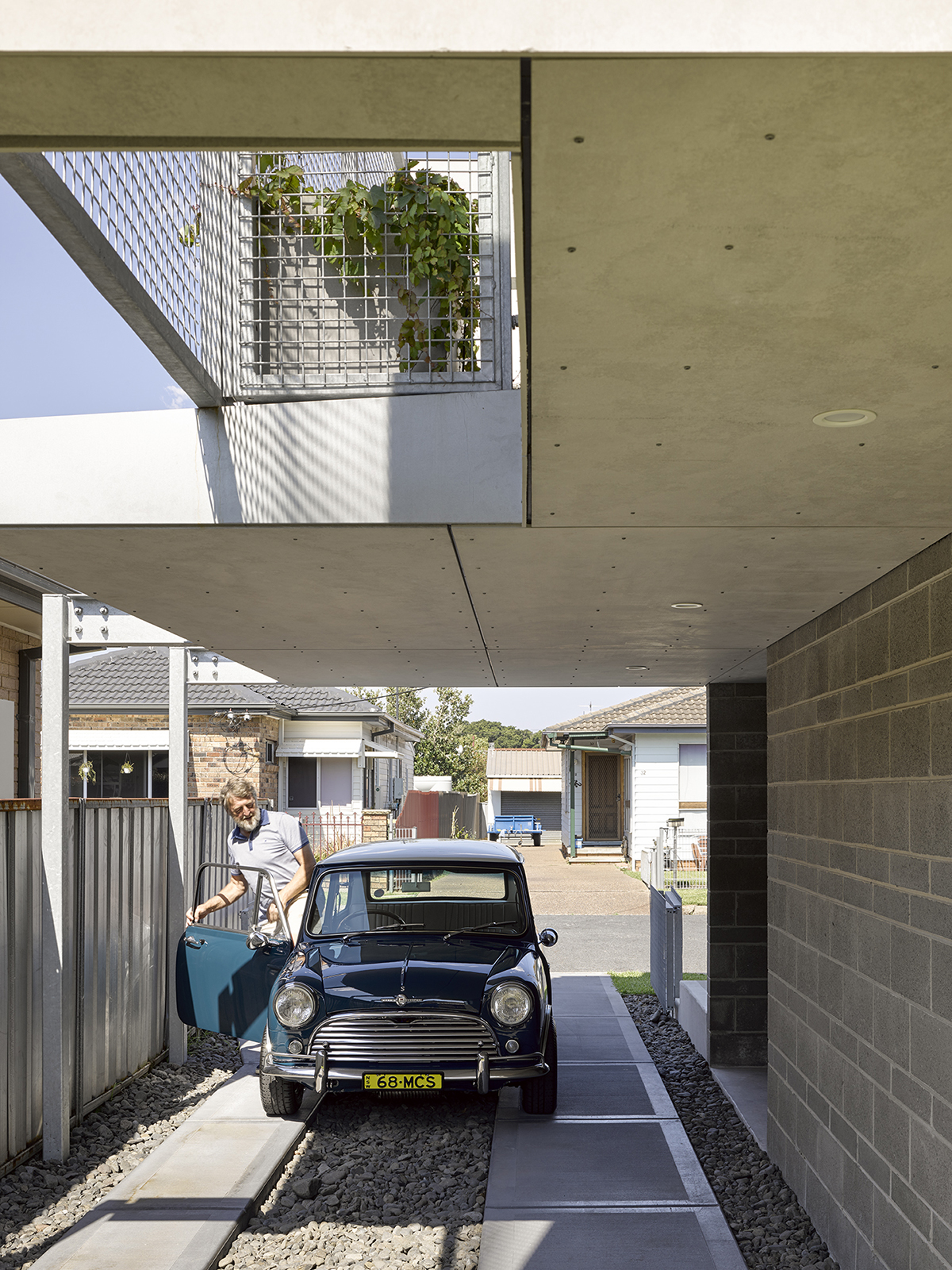 Image Of A Mini In A Carport With Light From Above And Planter Box Overhead.