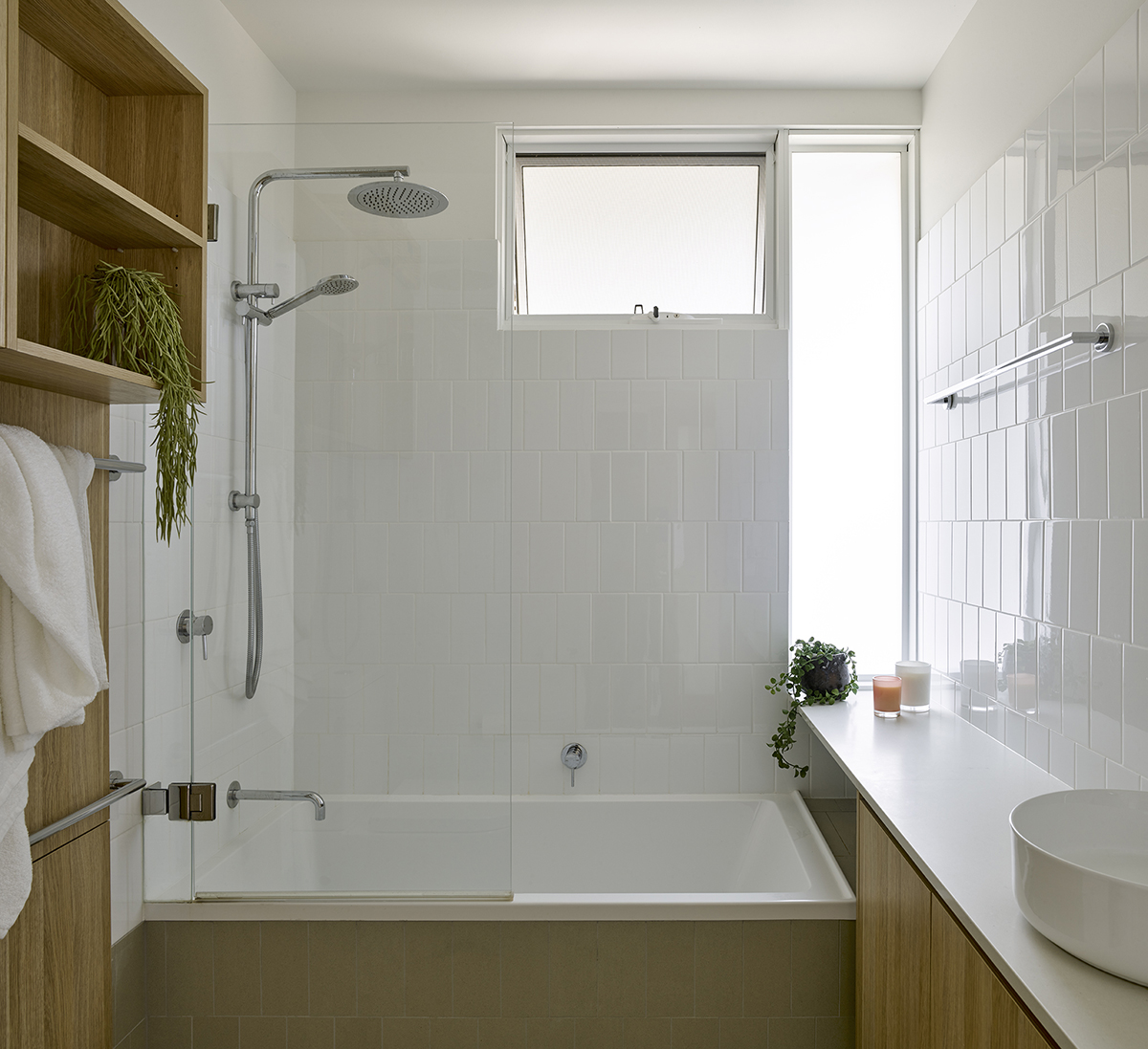 Image Of A Renovated Bathroom With White Tiles And Timber Cabinets.