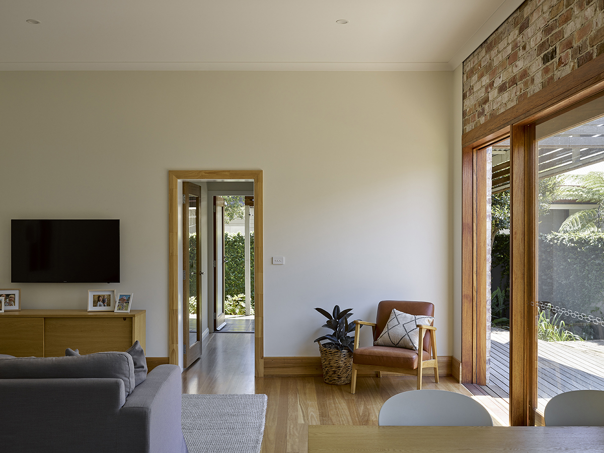 Image Of A Renovated Interior Showing Original Brickwork Above New Sliding Timber Door.