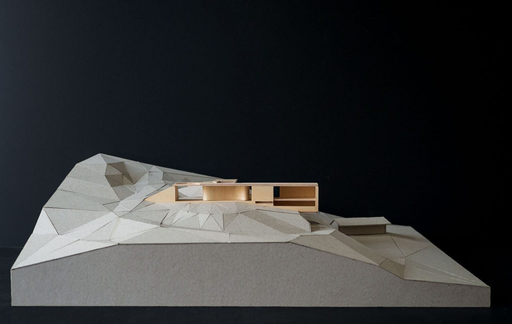 Image of a timber model of a house on a cardboard base.
